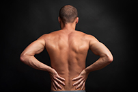 strong muscular man holding his naked back with hands - spine ache concept